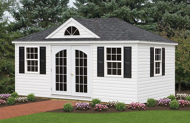 hip roof shed with large windows and double doors with glass panels sitting in a garden in maryland