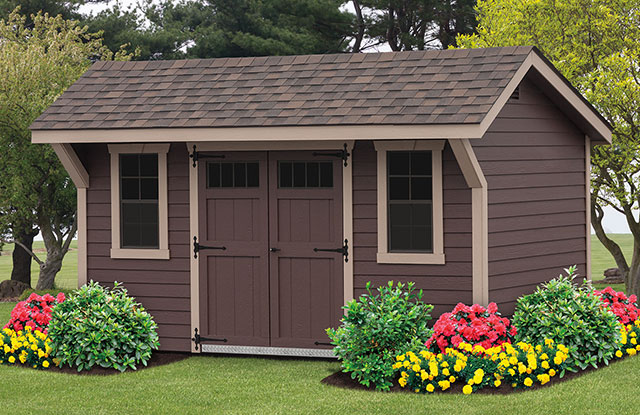 new haven series shed with overhang and brown siding sitting in a flowerbed in maryland