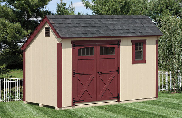 quaker series storage shed with red trim and doors in a freshly mowed backyard