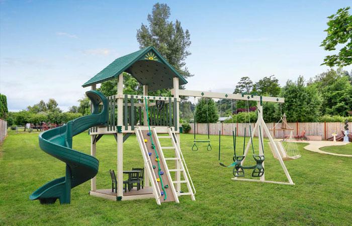 green vinyl swing set with climbing wall