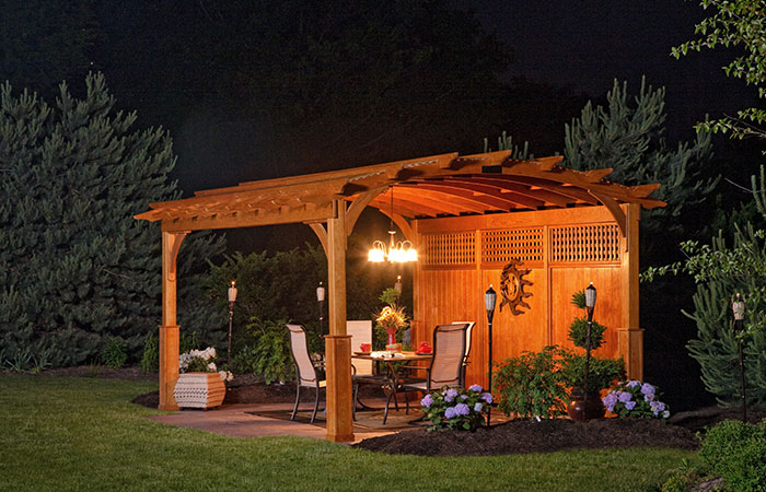 cedar pergola with large arch and exterior lighting