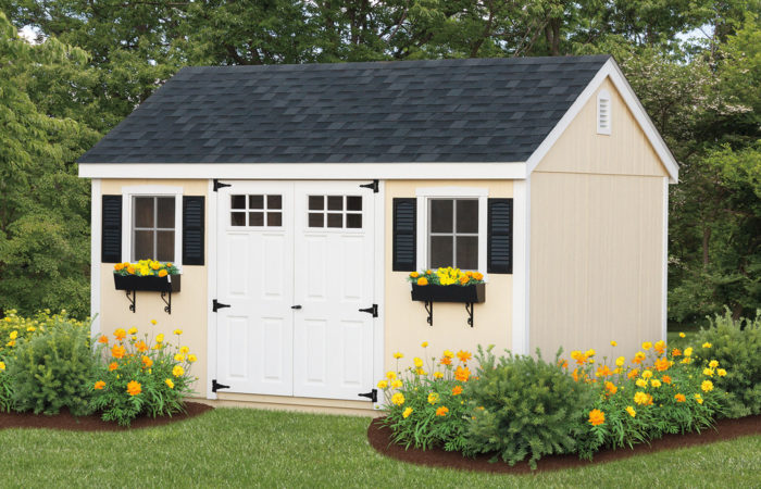 cream and navy storage shed with flower boxes in the window