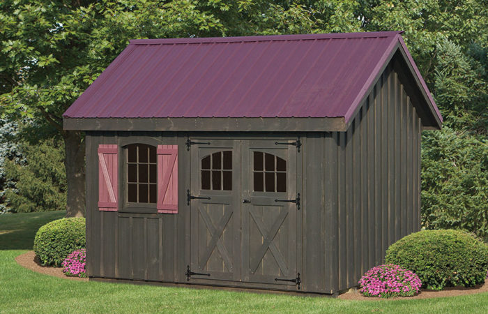 deep brown natural wood board and batten shed with maroon roof and shutters