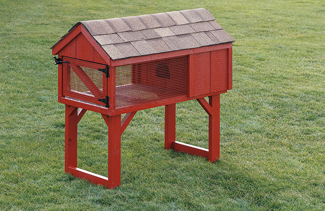red elevated wooden rabbit hutch