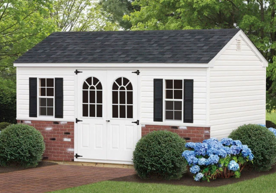 storage shed with white siding and decorative stone panel