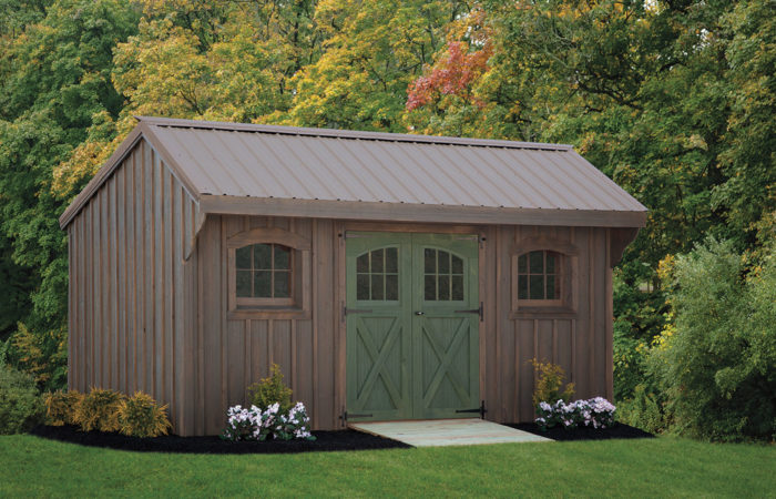 quaker series shed with weathered gray siding and green doors