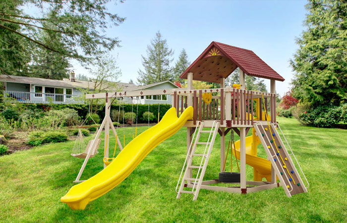 custom swing set with small climbing wall and multiple slides