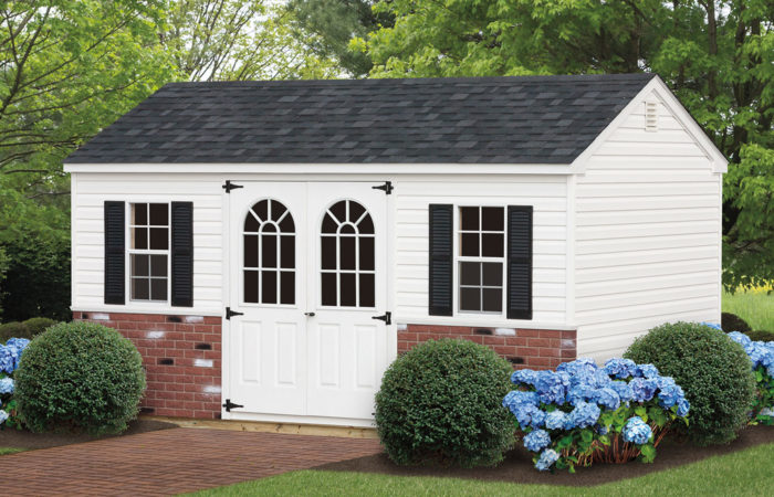 white a frame storage shed with brick panels