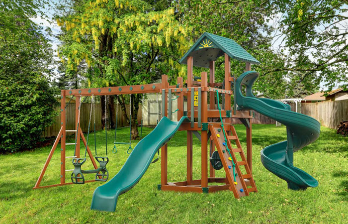 wooden swingset with two slides and small climbing wall