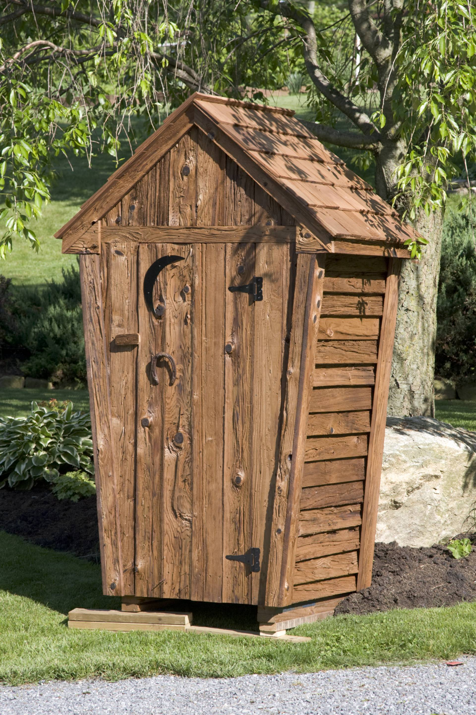 amish built outhouse with wood shingles and moon symbol