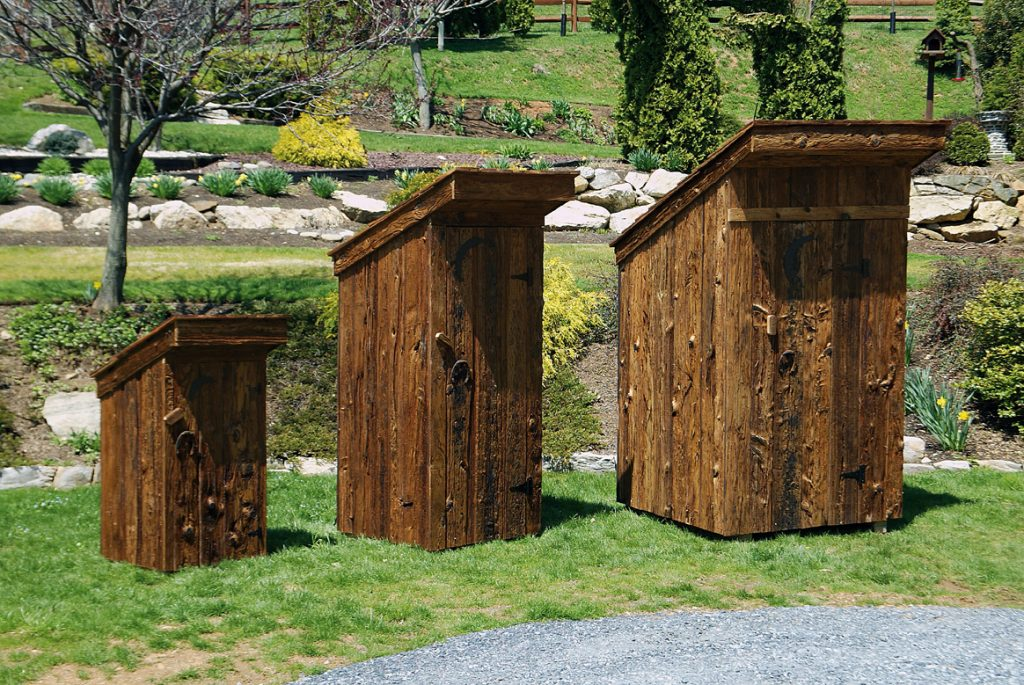 three different size amish built outhouses